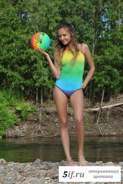 Миловидная девочка окунает попку в воду