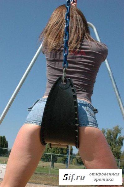 Голая молодая катается на качели в коротких шортиках