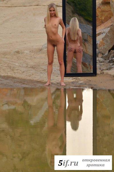 Позирует на пляже у зеркала